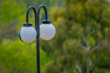 Close up of selective focus of public lamp located at outdoors of the blurred forest landscape in Pucon, Chile Stock Photo