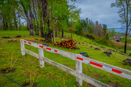 Outdoor view of of firewood pile with a wooden fence in Pucon in Chile