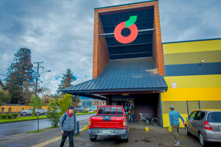 PUCON, CHILE - SEPTEMBER, 23, 2018: Tourists walking close to gorgeous wooden colonial buildings and some cars parked in the parking area, located in the city of Pucon