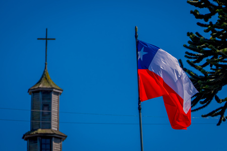 Exterior detail view of chilean flag waving with a blurred vilupulli church behind, wooden churches located at Chiloe island, Chile