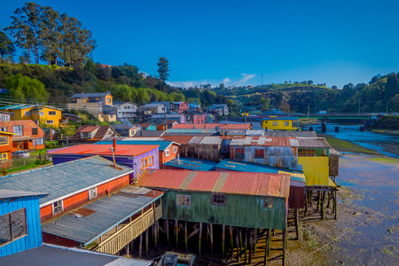 Above beautiful and colorful houses on stilts palafitos in Castro, Chiloe Island