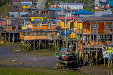 CHILOE, CHILE - SEPTEMBER, 27, 2018: Boat close to a houses on stilts palafitos in Castro, Chiloe Island, Patagonia