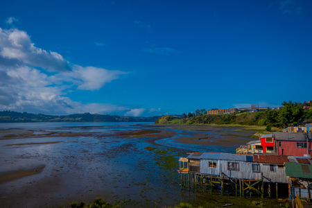 Outdoor view of beautiful coorful wooden houses on stilts palafitos, in a low tide day view in gorgeous sunny day in Castro, Chiloe Island Stock Photo