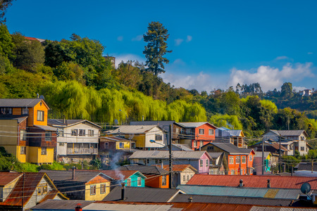 Outdoor view of colorful houses on stilts palafitos in the horizont located in Castro, Chiloe Island