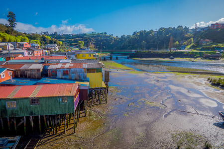 Outdoor view of beautiful coorful wooden houses on stilts palafitos, in a low tide day view in gorgeous sunny day in Castro, Chiloe Island in gorgeous blue sky.