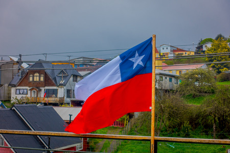 Outdoor view of Chilean flag waving with beautiful and colorful houses on stilts palafitos behind in the horizont in Castro, Chiloe Island, Chile. Stock Photo