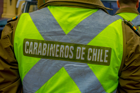 SANTIAGO, CHILE - SEPTEMBER 13, 2018: Back view of Police called as carabineros checking the crowd for segurity in front of la Moneda Palace, seat of the President in Santiago