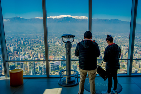 SANTIAGO, CHILE - OCTOBER 16, 2018: Inside view of of couple standing close to a coin viewer machine with the city of Santiago at San Cristobal Hill, the Andes Mountains stretching across the horizont