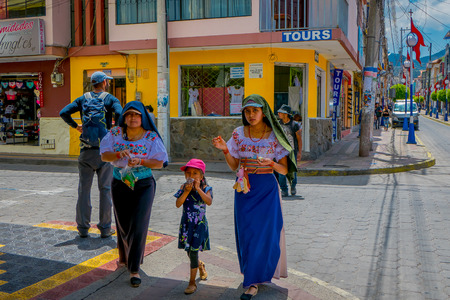 OTAVALO, ECUADOR, NOVEMBER 06, 2018: Family walking in the streets of the city of Otavalo wearing typical indigenous clothes