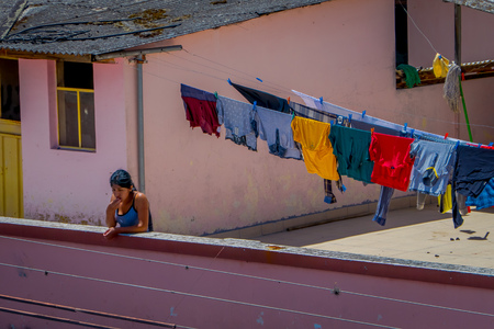 OTAVALO, ECUADOR, NOVEMBER 06, 2018: Outdoor view of unidentified woman close to a clothes drying in the sun in Otavalo