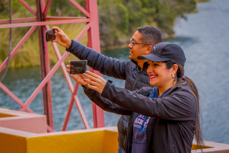 CUICOCHA, ECUADOR, NOVEMBER 06, 2018: Unidentified tourists taking selfies in front of the Cuicocha lake in the Province of Imbabura in Ecuador