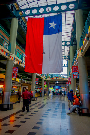 SANTIAGO, CHILE - OCTOBER 09, 2018: Unidentified people waiting inside of the terminal bus station with a Chilean flag hanging from rooftop. This is the largest and primary bus terminal of the city Éditoriale