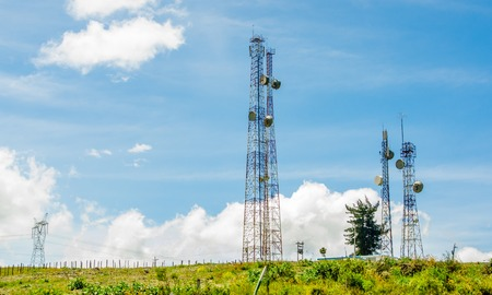 Telecommunication equipment on a blue sky background. Directional antenna for mobile phones. The concept of wireless communication. Tower with a communication repeater antenna. Repeater