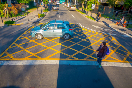 SANTIAGO DE CHILE, CHILE - OCTOBER 16, 2018: Above view of people using the zebra cross with traffic on the streets of the city in Santiago de Chile