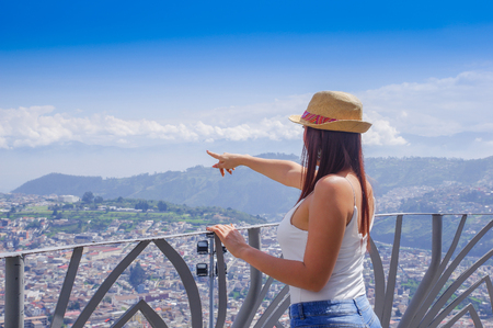 Back view of young woman wearing a panama hat and pointing with her hand a place and enjoying the panoramic view from el Panecillo on the historical centre of Quito