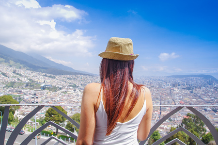 Back view of young woman wearing a panama hat and enjoying the panoramic view from el Panecillo on the historical centre of Quito