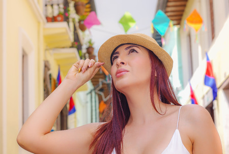 Portrait of beautiful young woman wearing a panama hat at historical center of old town Quito in northern Ecuador in the Andes mountains