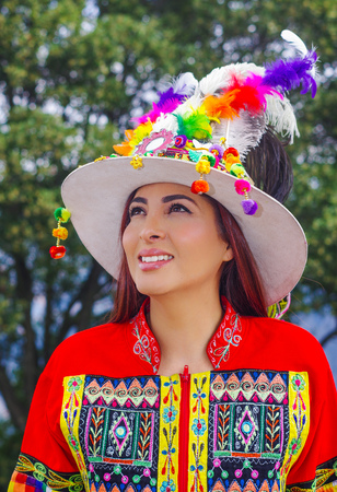 Portrait of beautiful young woman wearing typical folklore clothes used for festivity and dance in the street at historical center of old town Quito in northern Ecuador in the Andes mountains
