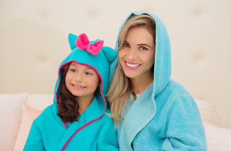 Portrait of smiling young mom and daughter wearing a blue bathrobes with hood