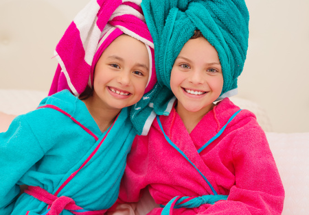 Little child having fun in front of big mirror after bath with towel on head Stock Photo