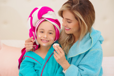 Mom aplying to her little daughter a cream in the face, wearing a blue bathrobes in the room
