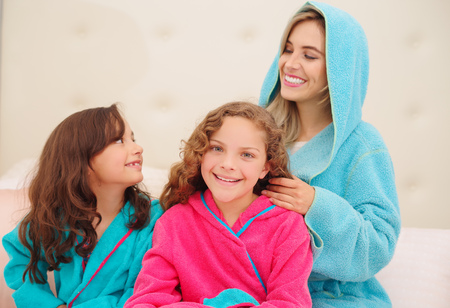 Close up of young mom brussing the hair of her little daugher who is wearing a blue bathtowel while her other curly girl is wearing a blue bathtowel and waiting for her turn