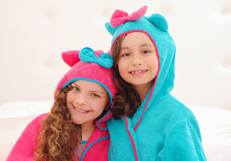 Portrait of two sister wearing a bathtowel with hood Stock Photo