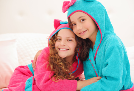 Portrait or two sister hugging each other and wearing bathtowels with hood Stock Photo