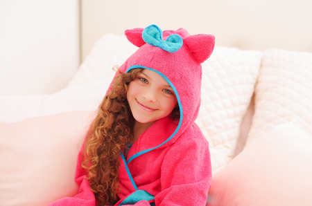 Portraiti of beautiful curly girl wearing a pink bathtowel with hood