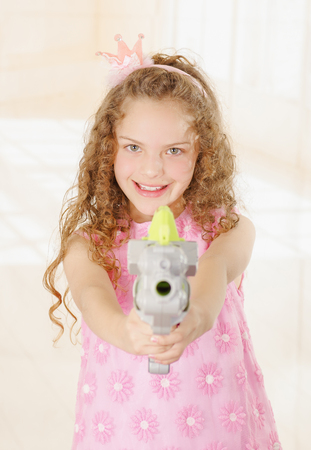 Happy little girl pointing a gun and wearing a pink princess dress Stock Photo