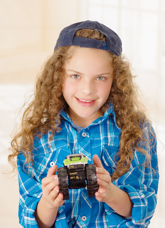 Close up of beautiful curly girl wearing boy clothes with hat and holding a car toy in her hand