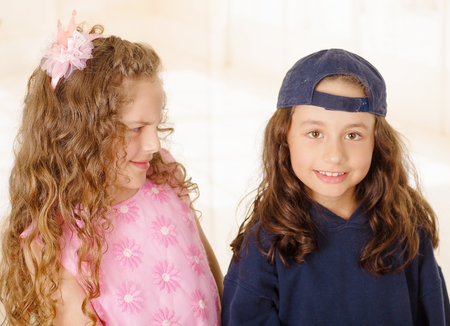 Close up of two girls, one is wering boy clothes and other girl is wearing a pink princess dress Stock Photo