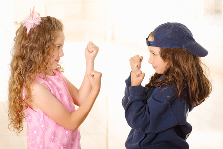 Close up of two girls, one is wering boy clothes and other girl is wearing a pink princess dress and doing fists and trying to fight Stock Photo