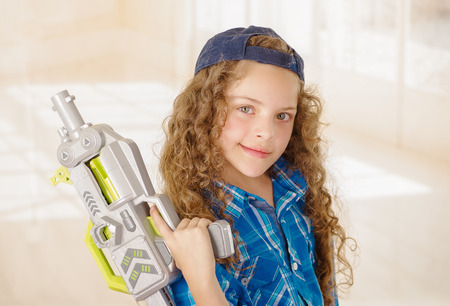 Close up of beautiful curly girl wearin boy clothes and holding in her hands a toy gun