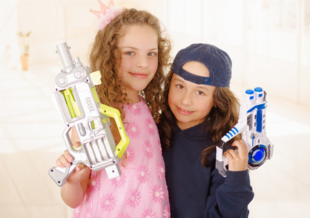 Close up of two girls one is wering boy clothes and holding a gun and other girl is wearing a pink princess dress
