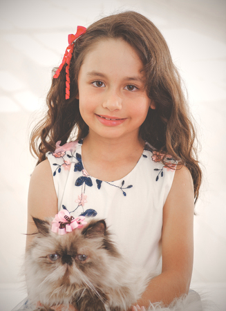 Portrait of beautiful smiling little girl hugging her cat