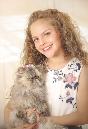 Portrait of beautiful smiling little curly girl hugging her cat