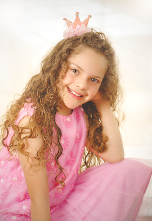Beautiful little curly girl posing for camera and wearing a pink princess dress