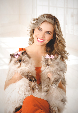 Portrait of elegant young woman holding two adorable Persian cats Stock Photo
