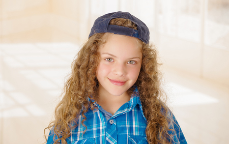Portrait of beautiful curly girl wearing boy clothes blue t-shirt and hat