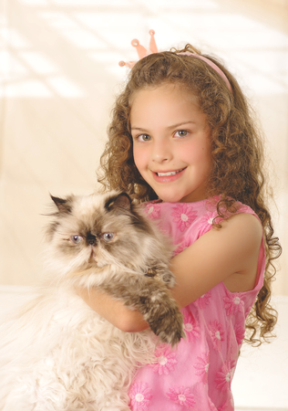 Beautiful little curly girl hugging her cat and wearing a pink princess dress Stock Photo