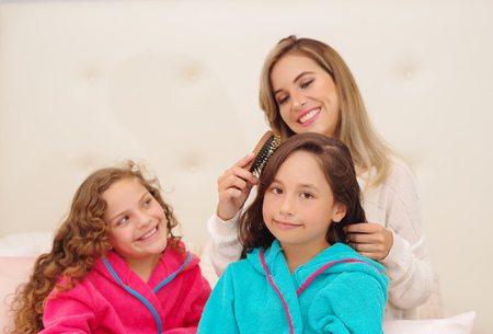 Close up of young mom brussing the hair of her little daugher who is wearing a blue bathtowel while her other curly girl is waiting for her turn
