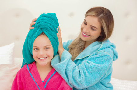 CXlose up of young mom aplying to her little daughter a blue towel in the head while both are wearing a bathrobes