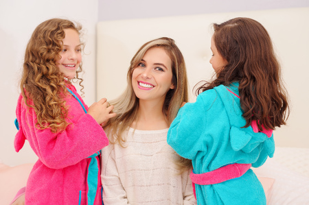 Close up of two litle girls playing with the hair of their mom, while curly girls is wearing a pink bathrope and brunette girl a blue bathrope