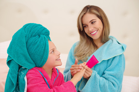 Close up of young mom gicing a massage to her little curly girl in a lady night home spa while both are wearing a bathrobes Stock Photo