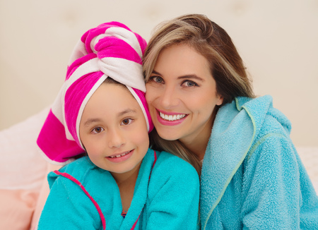 Mom and little daughter wearing a blue bathrobes in the room Stock Photo