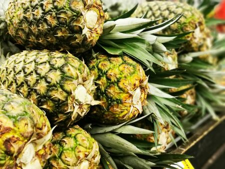 Pile pineapple fruit which has been harvested and display for sale on farmers table in market.