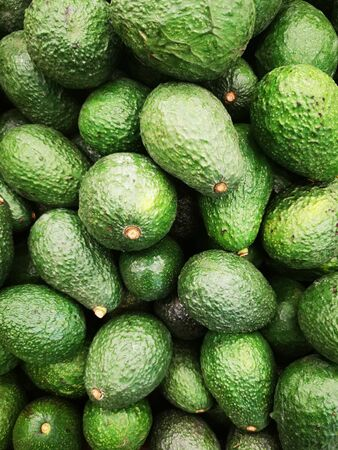 Closeup of bunch of fresh green avocado in the supermarket.