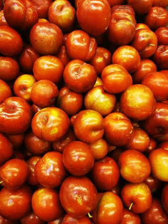 Ripe red greengages in a pile on a market Stock fotó