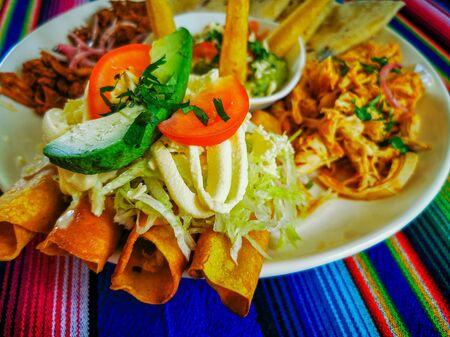 Mexican food mix colorful background, guacamole, cochinita pibil, flautas and quesadilla